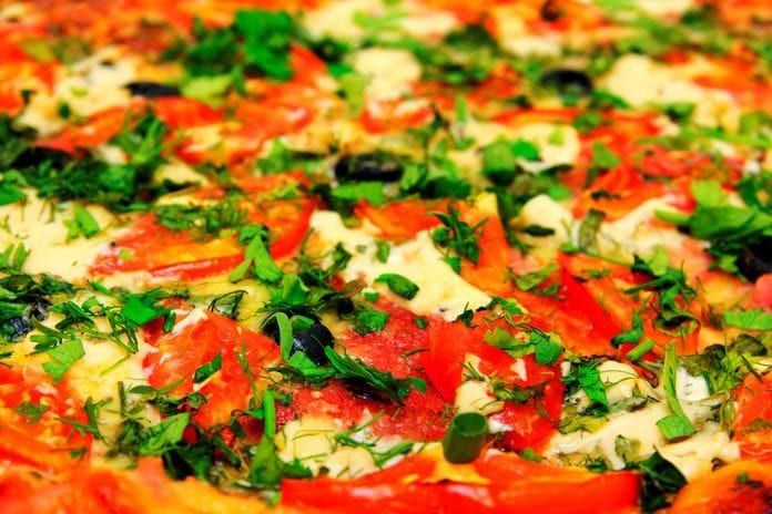 Close Up View On Pizza With Tomatoes And Greens